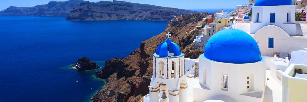 Blick auf ein griechisches Dorf am Meer. Im Vordergrund ist eine griechisch-orthodoxe Kirche mit blauen Kuppeln zu sehen.